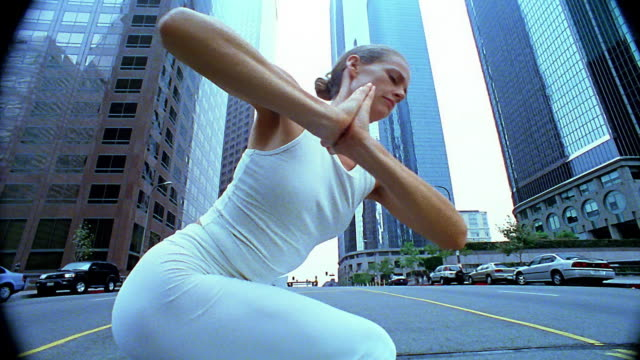 Medium shot tilt up woman doing yoga on city street with office buildings in background / Los Angeles