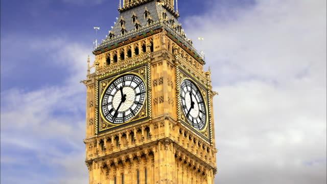 Medium shot time lapse clouds passing behind clock tower of Big Ben / London