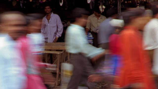 Medium shot time lapse crowds walking past street vendors / Nepal