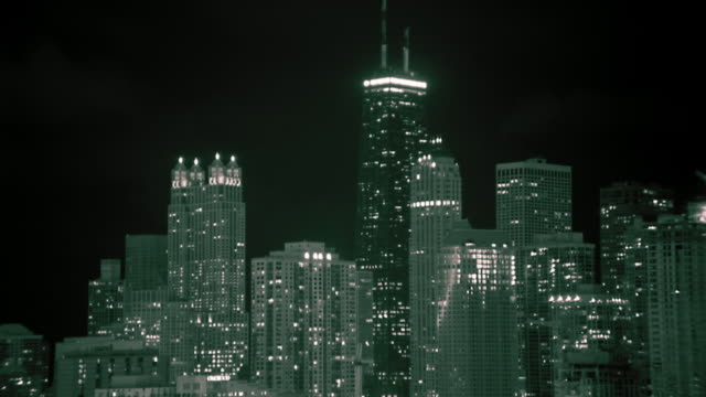 Medium shot time lapse fog moving over Hancock Building and other skyscrapers at night / Chicago