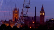 Medium shot time lapse Millennium London Eye Ferris Wheel turning with Big Ben and Parliament in background / dusk to night