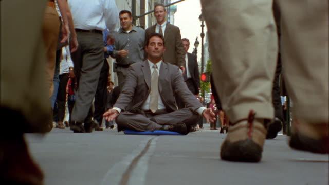 Medium shot time lapse pedestrians walking / businessman sitting in lotus position on sidewalk