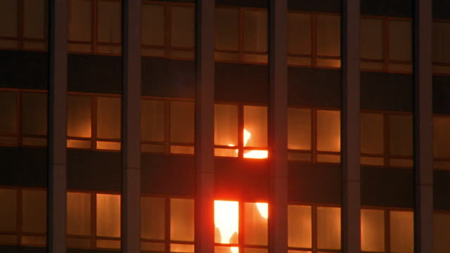 Medium shot time lapse reflections of sun rising in office building windows / New York City