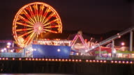Medium shot time lapse Santa Monica pier lit at night w/ferris wheel and amusement park / California