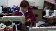 Medium shot time lapse woman sitting in front of sewing machine and applying glue to shoe fabric + folding them