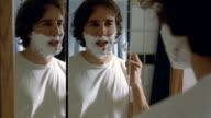 Medium shot tired man shaving in mirror / talking to himself and sighing