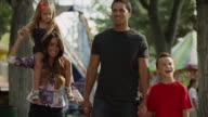 Medium shot to close up of family walking at carnival / American Fork, Utah, United States