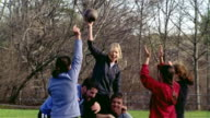 Medium shot touch football team carrying woman on their shoulders after she scores touchdown/ tilt up bare trees/ Maine