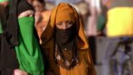 Medium shot tracking shot 2 women in veils walking and talking in street / Djemaa el Fna Square, Medina, Marrakesh