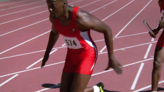 Medium shot tracking shot Black male runner passing baton to teammate during relay race