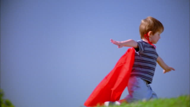 Medium shot tracking shot boy in red superhero cape running and pretending to fly w/arms outstretched