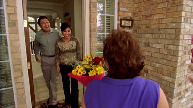Medium shot tracking shot couple carrying flowers and wine being greeted by friends at door / couples entering house