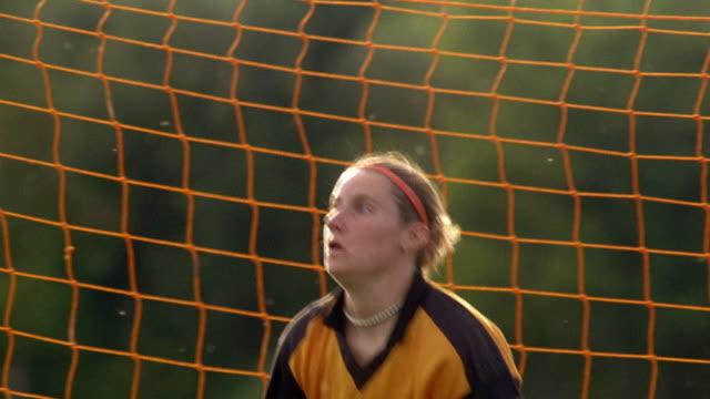 Medium shot tracking shot female teenage goalie diving and catching soccer ball / Vermont