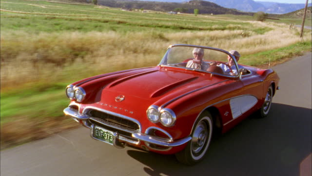 Medium shot tracking shot front view senior couple driving in 1960s Corvette convertible and waving at CAM
