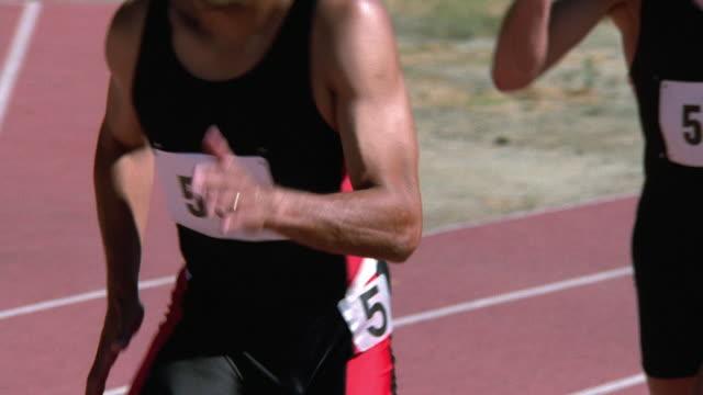 Medium shot tracking shot male runner passing baton to teammate during relay race
