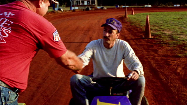 Medium shot tracking shot man presents trophy to other man sitting on lawn mower, winner raises trophy / Alabama