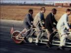 1964 medium shot tracking shot men riding on 11-person tandem bicycle