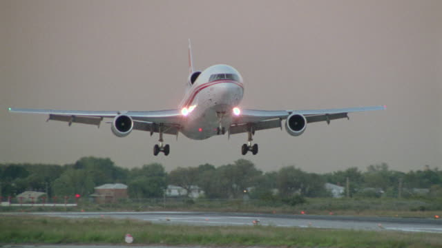 Medium shot tracking shot passenger jet landing on runway with zoom out to close up wheels on tarmac at dusk / New York