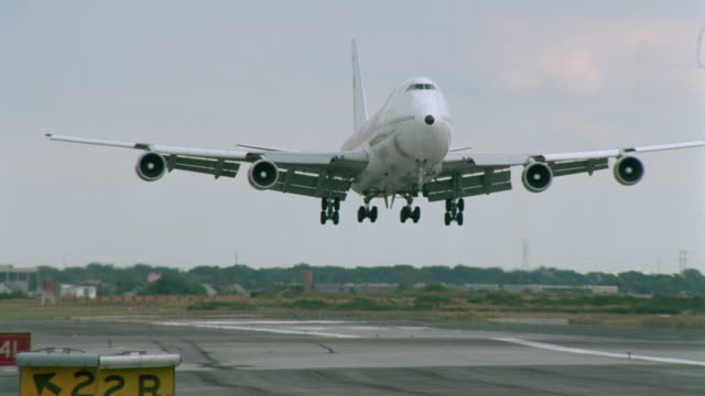 Medium shot tracking shot passenger jet landing on runway with zoom out to close up wheels on tarmac / New York