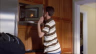 Medium shot tracking shot teenage boy removing food from microwave / leaning forward and eating from container on counter