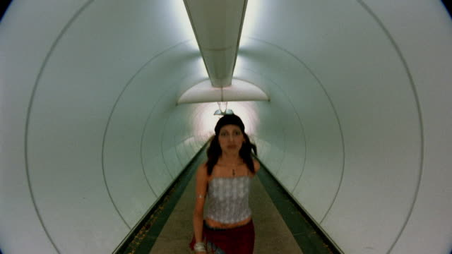 Medium shot tracking shot young Asian woman walking through tunnel