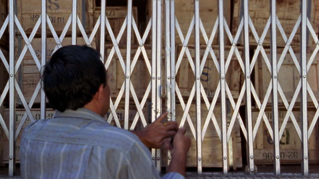 Medium shot truck driver padlocking truck door / uniformed men locking outer truck doors / Indonesia