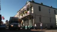 Medium Shot - Trucks driving down narrow Bourbon Street / New Orleans Louisiana