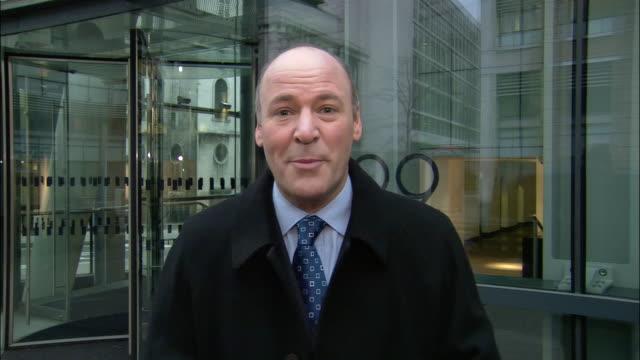 Medium shot TV reporter talking to camera in front of modern, glassy building/ London
