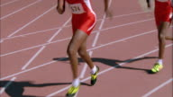 Medium shot two Black male runners passing baton in track relay race