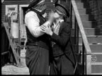 1918 B/W Medium shot two blindfolded men kiss each other, remove blindfolds, then begin to fight