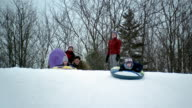 Medium shot two boys and girl sledding down hill on inner tubes / father giving daughter a push