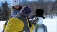 Medium shot two children building snowman / boy sticking carrot onto face of snowman / Vermont