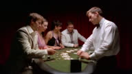 Medium shot two men and two women sitting at blackjack table / dealer dealing cards / paying winners