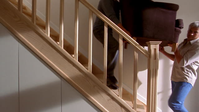 Medium shot two men carrying chair up wooden stairs against white wall