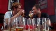 Medium shot two men holding glasses w/beer and talking in bar w/table full of empty glasses in foreground