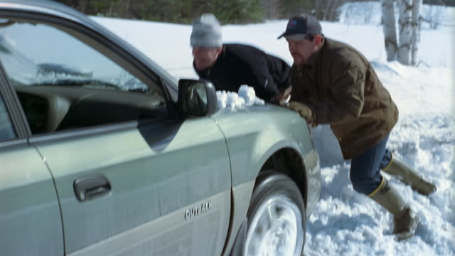 Medium shot two men pushing car stuck in snowbank / Vermont