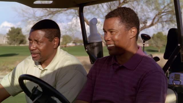 Medium shot two men riding in golf cart and talking