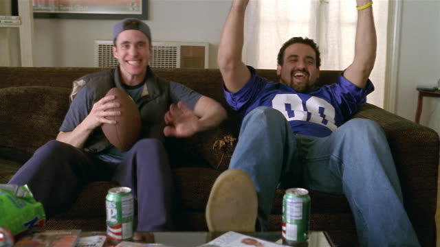 Medium shot two men sitting on sofa and watching football game on TV / cheering / talking to someone offscreen