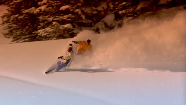 Medium shot two people snow boarding past evergreen trees and toward camera on mountainside / Aspen, Colorado