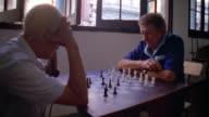 Medium shot two senior Hispanic men playing chess / Cuba