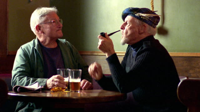 Medium shot two senior men sitting at table in pub drinking beer and talking / one smokes pipe / Nova Scotia