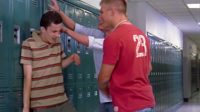 Medium shot two teenage boys hanging boy on locker by shirt