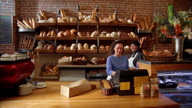 Medium shot two women behind bakery counter / woman carries basket of fresh rolls / Seattle, Washington