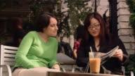 Medium shot two women looking through magazine at sidewalk cafe / Seattle