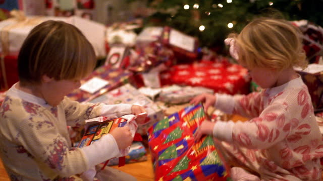 Medium shot two young boys and girl in pajamas opening gifts with Christmas tree in background