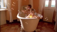 Medium shot two young boys sitting in bathtub and trying to catch bubbles floating in air