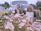 1939 Medium shot Two young girls standing in field of flowers in front of old car in Griffith Park / Los Angeles, California, USA