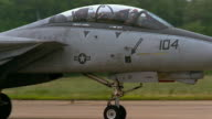 Medium shot US Navy jet fighter maneuvering on runway