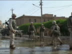 2003 medium shot US soldiers standing on watery street with barbed wire running across it / Baghdad Iraq