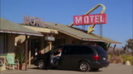 Medium shot van driving up to entrance of motel / family exiting from van, stretching and looking around